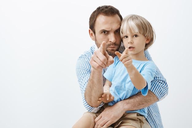 Zabawny troskliwy europejski ojciec, trzymający i przytulający słodkiego synka z bielactwem, wskazujący, marszczący brwi i robiąc miny