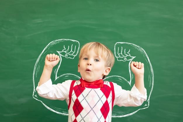 Zabawny uczeń dziecko w klasie przed zieloną tablicą. wychowanie fizyczne.