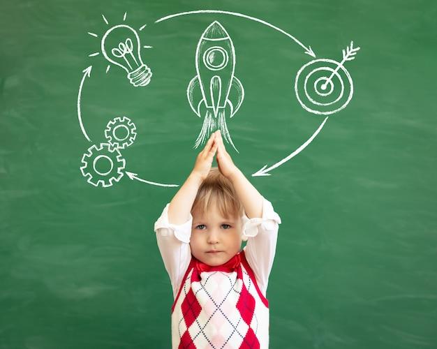 Zabawny uczeń dziecko w klasie przed zieloną tablicą.