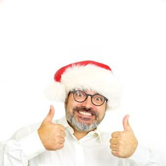 Zabawny uśmiechnięty przystojny brodaty mężczyzna w kapeluszu i okularach bożego narodzenia
