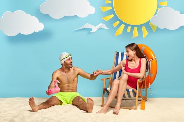 Zabawny, zachwycony wczasowicz mężczyzna siedzi na ciepłym piasku