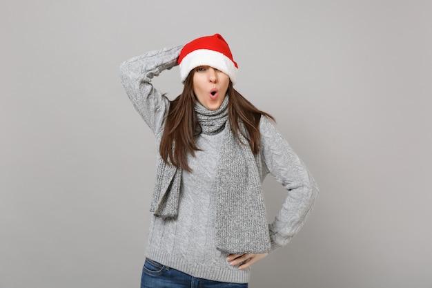 Zabawny zdumiony młoda dziewczyna santa w swetrze, szalik zakrywający oko z świątecznym kapeluszem, utrzymując szeroko otwarte usta na białym tle na szarym tle w studio. szczęśliwego nowego roku 2019 celebracja party wakacje koncepcja.