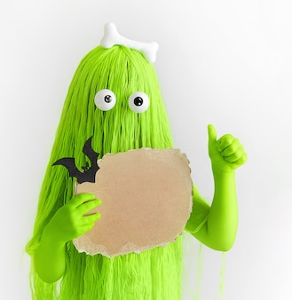 Zabawny zielony wielkooki potwór z kością na głowie i tekturą w dłoniach, pokazujący jak znak.