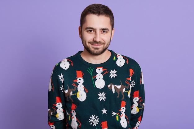 Zabawny zimowy człowiek w ciepłe ubrania pozowanie na białym tle nad ścianą bzu
