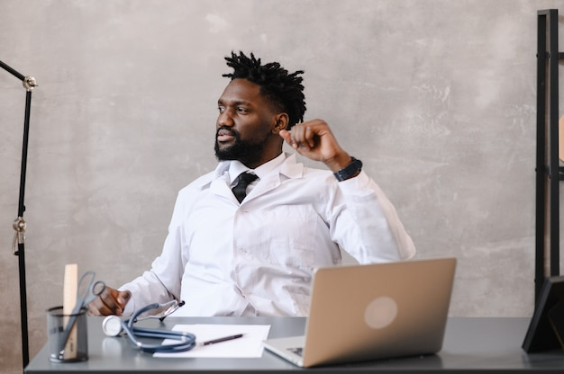 Zabawny znudzony w pracy afroamerykański lekarz pracownik zasypiający przy biurku, pracownik śpiący w miejscu pracy w pobliżu laptopa czuje się przepracowany koncepcja