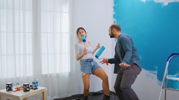 Zabawy dekorowanie salonu mieszkania. pędzel rolkowy z niebieską farbą. remont mieszkania i budowa domu podczas remontu i modernizacji. naprawa i dekorowanie.