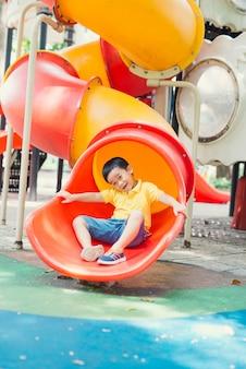 Zabawy dla dzieci na koncepcji placu zabaw. azjatycki chłopiec dziecko bawi się i uśmiecha na suwaku w parku zabaw w szkole rano