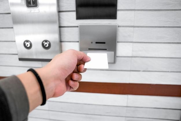 Zabezpieczając kontrolę dostępu do windy lub windy, ręka mężczyzny trzyma kartę klucza ułożoną w celu włożenia do uchwytu karty w celu odblokowania drzwi windy przed podniesieniem lub opuszczeniem.