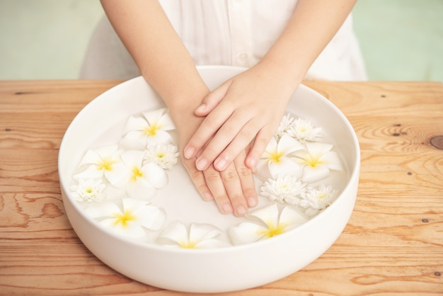 Zabieg i produkt uzdrowiskowy. białe kwiaty w ceramicznej misce z wodą do aromaterapii w spa.