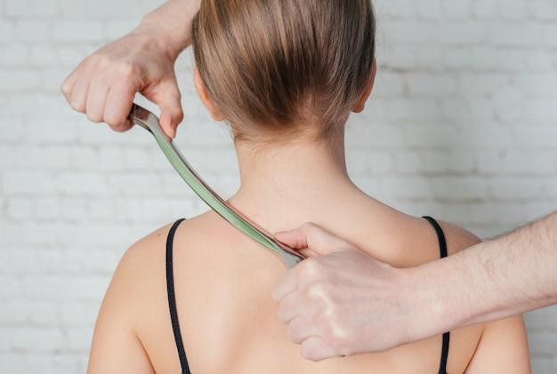 Zabieg iastm, dziewczynka poddana zabiegowi na tkankach miękkich na szyi narzędziem ze stali nierdzewnej