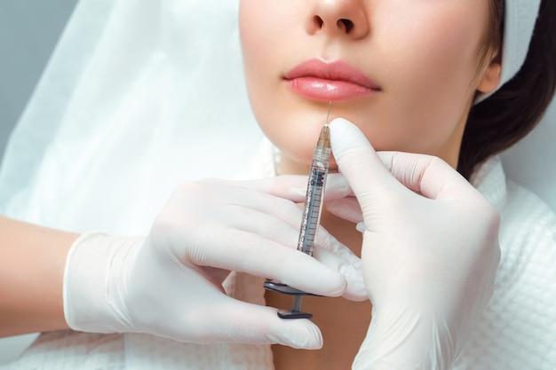 Zabieg korekcji kształtu ust w gabinecie kosmetycznym. specjalista wykonuje zastrzyk w usta pacjenta. powiększanie ust.