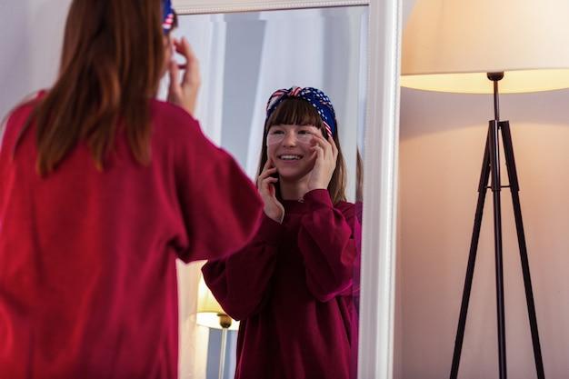 Zabieg kosmetyczny. miła dziewczyna utrzymująca uśmiech na twarzy, dbająca o swoją skórę