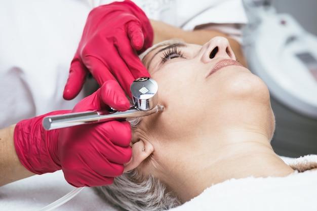 Zabieg kosmetyczny na twarz pięknej kobiety senior z tlenowym peelingiem naskórkowym w kosmetycznym gabinecie kosmetycznym.