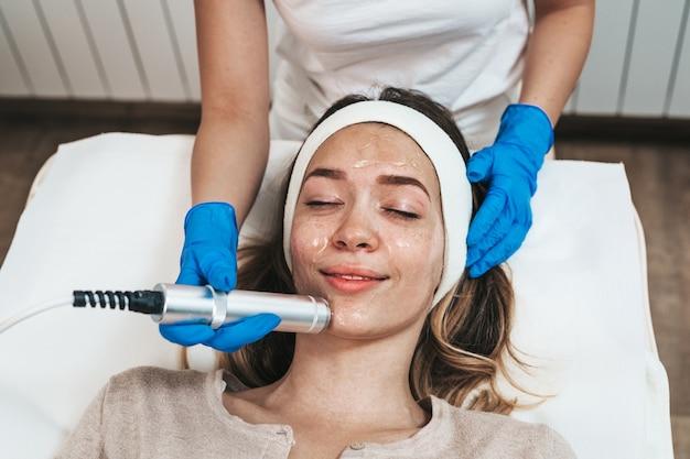 Zabieg kosmetyczny na twarz pięknej młodej kobiety z tlenem w kosmetycznym gabinecie kosmetycznym.