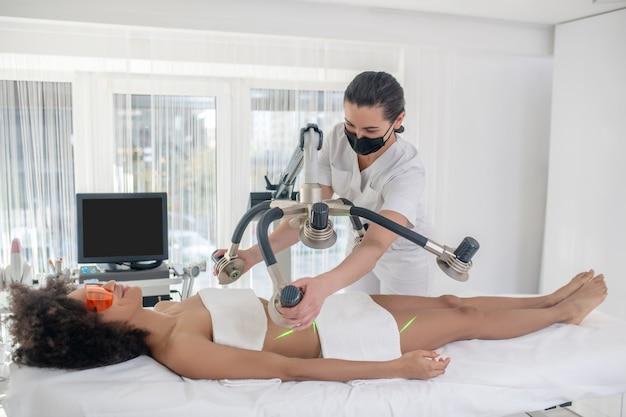 Zabieg kosmetyczny. uśmiechnięta dziewczyna w okularach ochronnych, leżąc na kanapie i kosmetyczka stojąca zakładanie aparatu laserowego