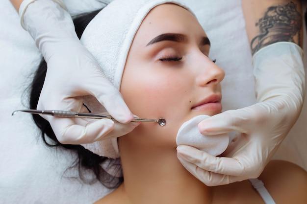 Zabieg mechanicznego lub ręcznego oczyszczania twarzy przez kosmetyczkę profesjonalny peeling skóry