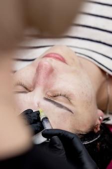 Zabieg mezoterapii twarzy w gabinecie kosmetycznym. lekarz kosmetyczka robi zastrzyki w skórę twarzy kobiety. mezoterapia, biorewitalizacja. zbliżenie. selektywne skupienie.