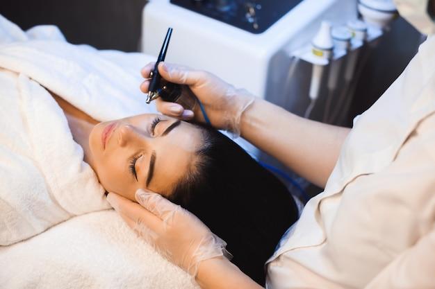 Zabieg na twarz nowoczesną aparaturą na twarz uroczej kaukaskiej pani w salonie spa