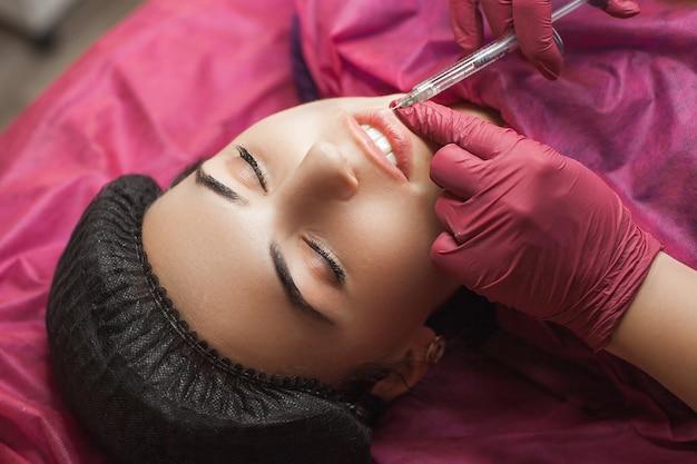 Zabieg powiększania ust w gabinecie kosmetycznym. kosmetolog wykonujący zastrzyk kwasu hialuronowego w celu wzmocnienia ust.