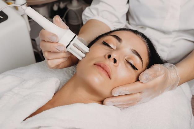 Zabieg przeciwstarzeniowy twarzy wykonany w salonie na twarzy brunetki rasy kaukaskiej