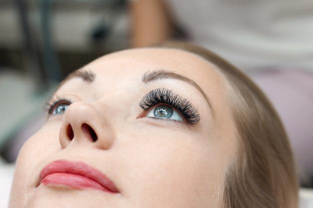 Zabieg przedłużania rzęs. kobieta oko z długimi rzęsami. ścieśniać