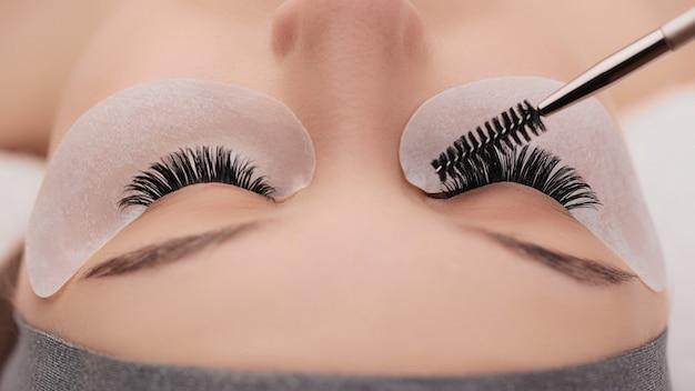 Zabieg przedłużania rzęs z bliska. sztuczne rzęsy. koncepcja makijażu i urody.