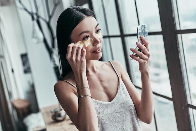 Zabieg upiększający. atrakcyjna młoda kobieta używająca opasek na oczy i uśmiechająca się podczas spędzania czasu w domu