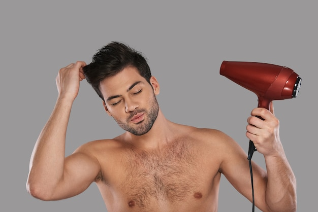 Zabieg upiększający. przystojny młody mężczyzna suszy włosy stojąc na szarym tle