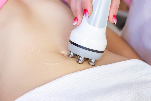 Zabieg usuwający cellulit na brzuchu kobiety, masaż kawitacyjny brzucha