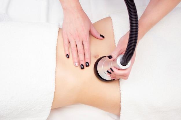 Zabieg usuwający cellulit z kobiecego brzucha, kawitacyjny masaż brzucha. masaż ultradźwiękowy do odchudzania. korekta kobiecej sylwetki bez interwencji chirurgicznej. zbliżenie na brzuch.