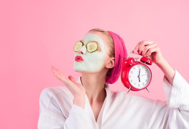 Zabiegi kosmetyczne kobieta z kosmetyczną maską na twarzy trzyma zegar kosmetyczny z naturalnym ogórkiem