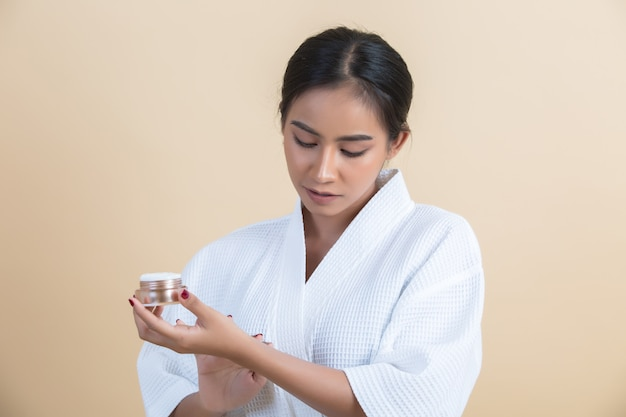 Zabiegi kosmetyczne z kobietą trzyma w dłoni krem nawilżający