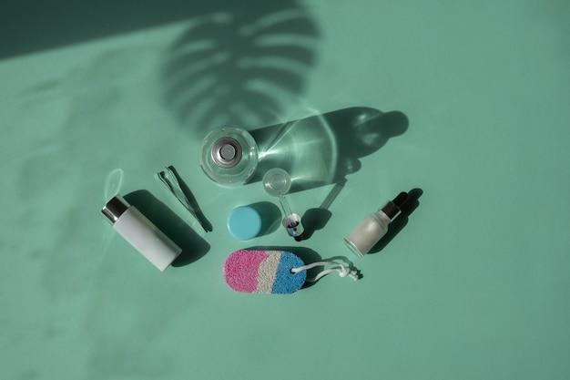 Zabiegi na ciało i spa. naturalne kosmetyki. eko krem, serum, pusta butelka do pielęgnacji skóry. pipeta szklana. pumeks do stóp. widok z góry.