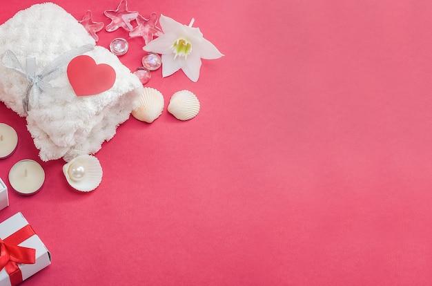 Zabiegi spa jako prezent na walentynki. biały ręcznik z kwiatkiem, muszelkami i perłą na czerwonym tle z sercem i prezentami. salon piękności, masaż. -