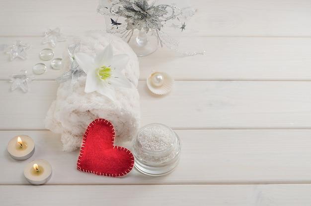 Zabiegi spa na walentynki. biały ręcznik z kwiatkiem i perłami na białym drewnianym stole z czerwonym sercem i świecami z miejscem na kopię. salon piękności, masaż.