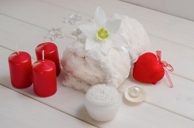 Zabiegi spa na walentynki. biały ręcznik z kwiatkiem i perłami na białym drewnianym stole z czerwonym sercem i świeczkami. salon piękności, masaż.