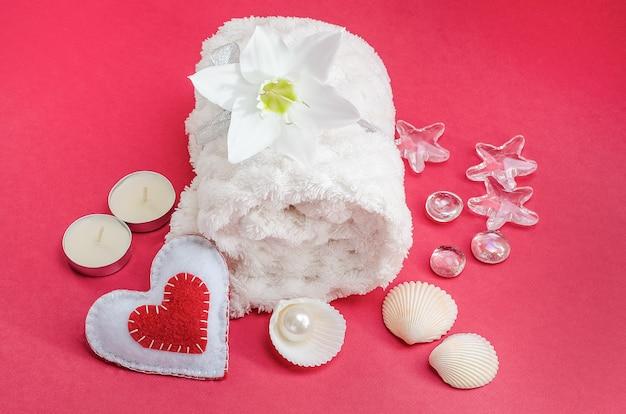 Zabiegi spa na walentynki. biały ręcznik z kwiatkiem, muszelkami i perłą na czerwonej powierzchni z sercem i świeczkami. salon piękności, masaż. -