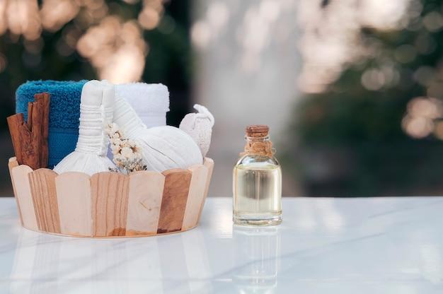 Zabiegi spa ustawione w drewnianym wiadrze z ziołową kulką kompresyjną, butelką z olejem, świecami i ręcznikiem na marmurowym blacie