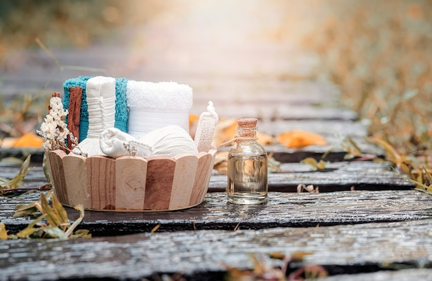 Zabiegi spa w drewniane wiadro z ziołową kulką kompresyjną, butelką oleju, świecami i ręcznikiem na mokrym tle przyrody.