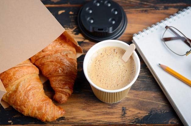 Zabierz filiżankę kawy z rogalikiem na drewnianym stole.