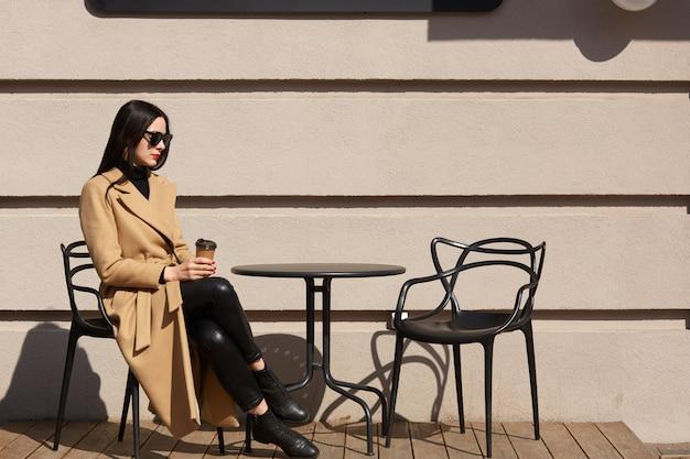 Zabierz kawę w ręce kobiet. piękna młoda brunetki kobieta jest ubranym brown żakieta obsiadanie przy stołem w ulicznej plenerowej kawiarni