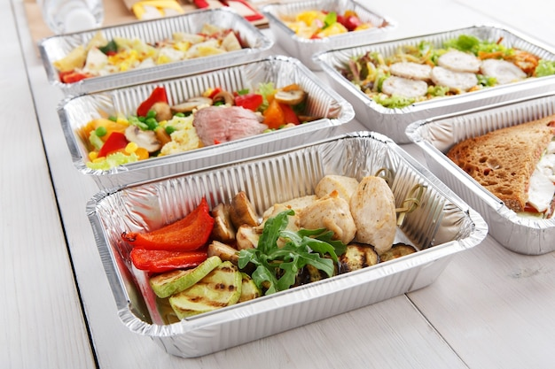 Zabierz naturalną żywność organiczną w foliowych pudełkach. sałatki mięsno-warzywne. widok z góry, płaski układ.