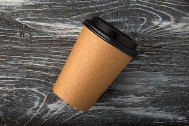 Zabierz papierowy kubek do kawy na szarym tle drewnianych z góry