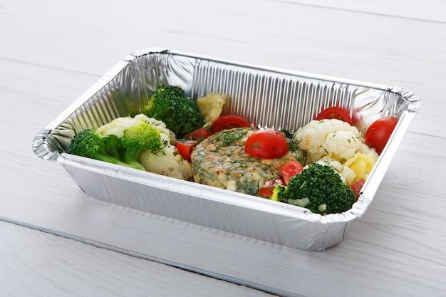 Zabierz posiłek. obiad w pudełkach foliowych. kotlet warzywny z kalafiorami, pomidorkami koktajlowymi i brokułami na białym drewnie