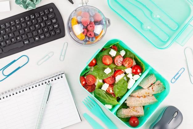 Zabierz pudełko na lunch ze świeżą sałatką i tuńczykiem nad biurkiem z artykułami biurowymi.