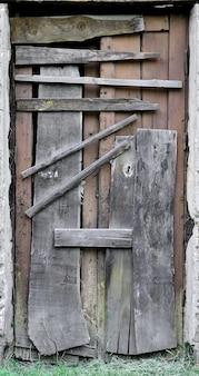 Zabite deskami drewniane drzwi do starego opuszczonego domu