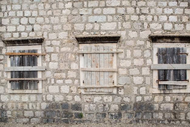 Zabite deskami okna w starym kamiennym budynku w czarnogórze