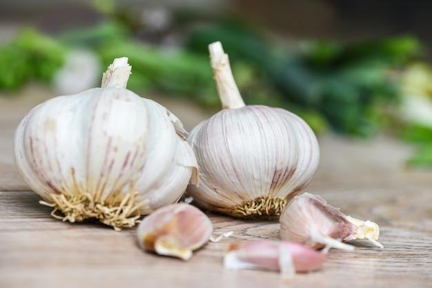 Ząbki czosnku i świeża cebula czosnkowa na drewnianych przyprawach i składnikach przypraw korzennych potraw