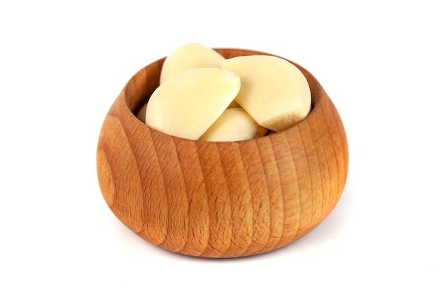 Ząbki czosnku w drewnianej misce na białej, zdrowej żywności
