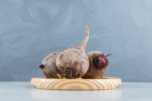 Ząbkowane rzodkiewki w drewnianym talerzu, na marmurowym tle.